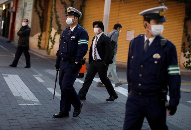 Police officers wearing protective face masks patrol on the street following the coronavirus disease outbreak in Tokyo
